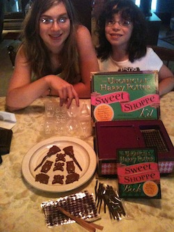 Two girls pose with the contents of the The Unofficial Harry Potter Sweet Shoppe Kit by Dinah Bucholz and finished chocolate candies