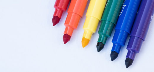 The tips of six markers (red, orange, yellow, green, blue, and purple) without lids are lined up in the upper-right corner on a white background.