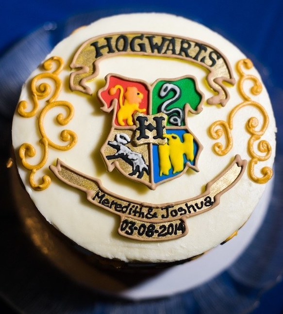 A white wedding cake with the colorful Hogwarts crest that says Meredith and Joshua