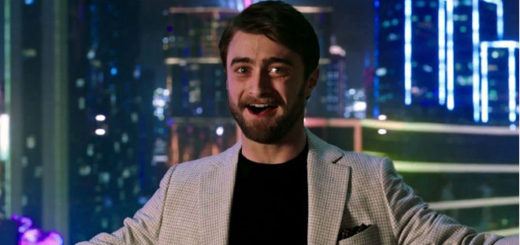 Daniel Radcliffe is tech tycoon Walter Mabry in Now You See Me. He is smiling gleefully and irritatingly at the camera with a big city in the background outside his penthouse's window behind him.