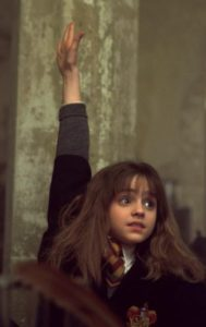 Hermione raising her hand in class