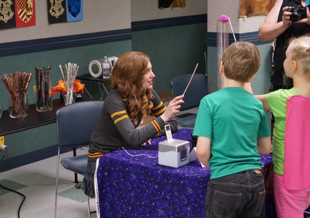 Hermione cosplayer and children testing free wands at library event