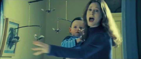 Lily Potter holds infant Harry Potter and looks terrified as Lord Voldemort enters Harry's nursery