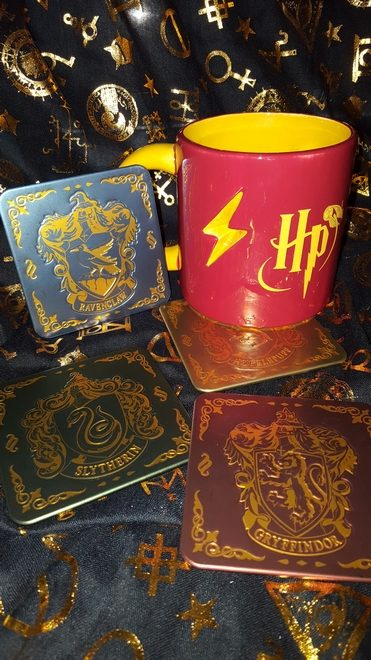 """Hogwarts House crests and a red and gold """"Harry Potter"""" coffee mug with a lightning bolt cut out"""