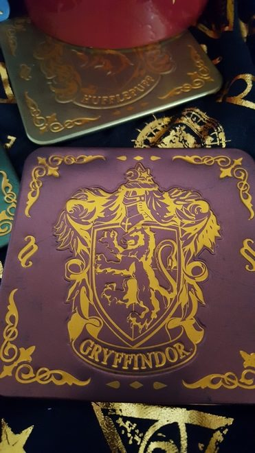 Gryffindor coaster in maroon and gold, with Hufflepuff coaster in yellow and gold
