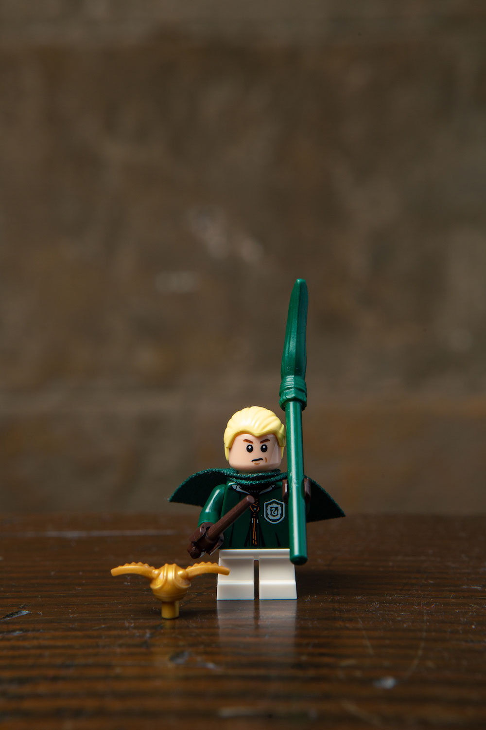 Draco's LEGO minifigure is dressed in his Quidditch uniform and a matching green broomstick – all of which his father bought him, of course.