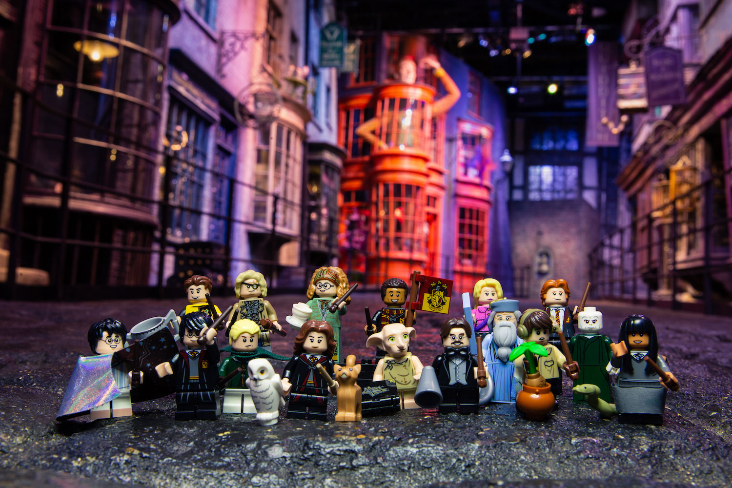 "All of the figures included in the ""Harry Potter"" group of LEGO minifigures pose in front of Diagon Alley at the Studio Tour."