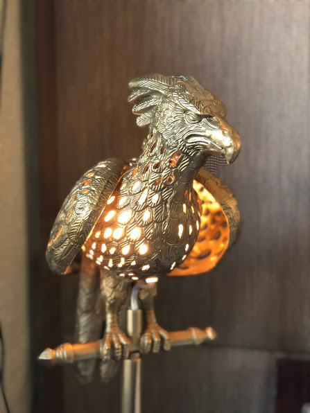 A golden lamp in the shape of the phoenix with holes in the feathers for light to shine through