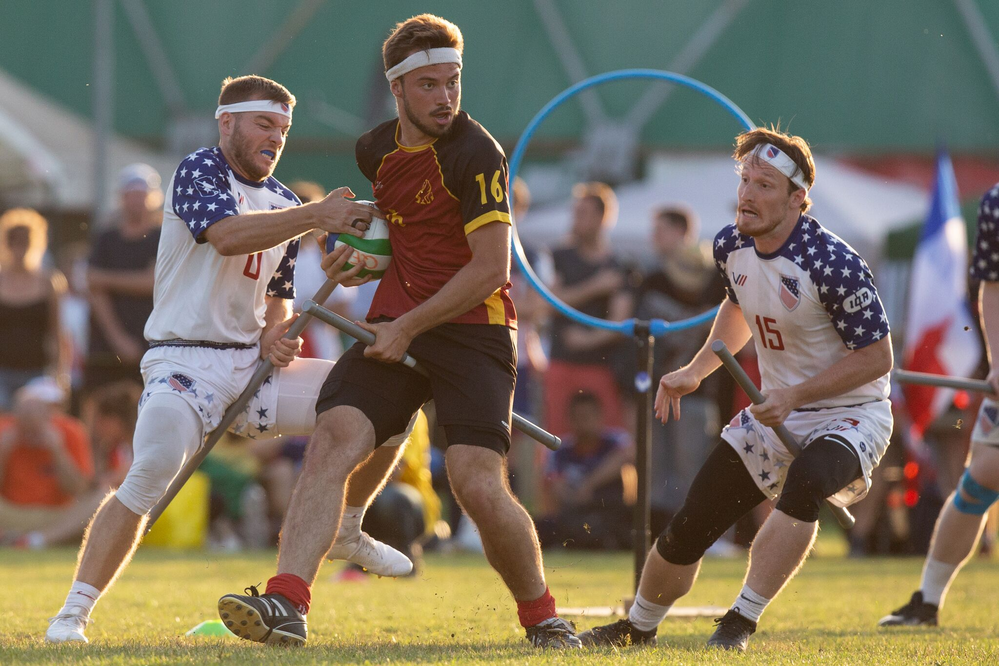 Chaser Andrew Axtell attempts to strip away the Quaffle from Belgium with Luke Langlinais on his right, during USA vs. Belgium