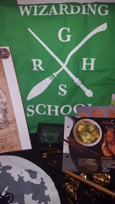 Geek Gear July 2018: Slytherin tote bag showing a wand and broom crossed, with an initial of each House in the blank space between the wand and broom. Words on the tote say: Wizarding School
