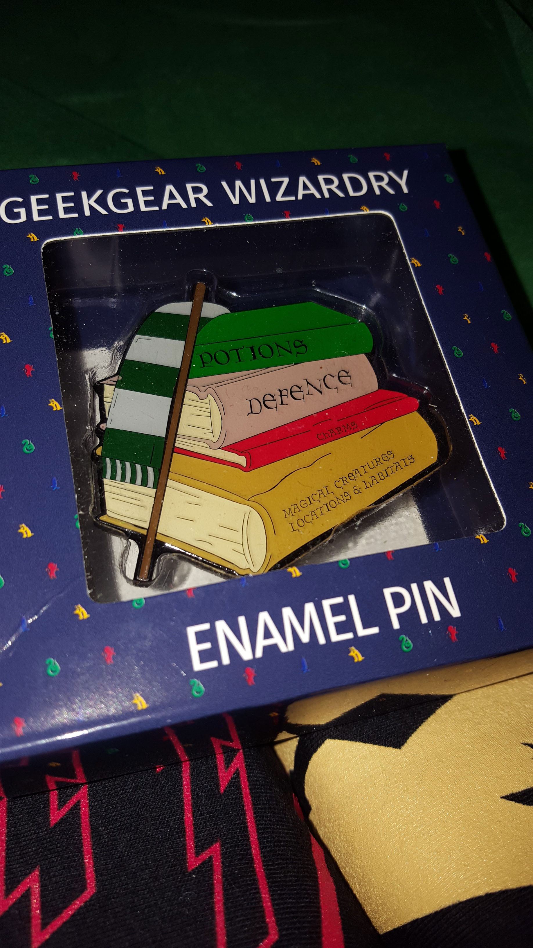 """Slytherin enamal pin featuring Slytherin scarf, wand, and stack of """"Potions"""", """"Defence"""", """"Charms"""", and """"Magical Creatures, Locations, & Habitats"""" books"""