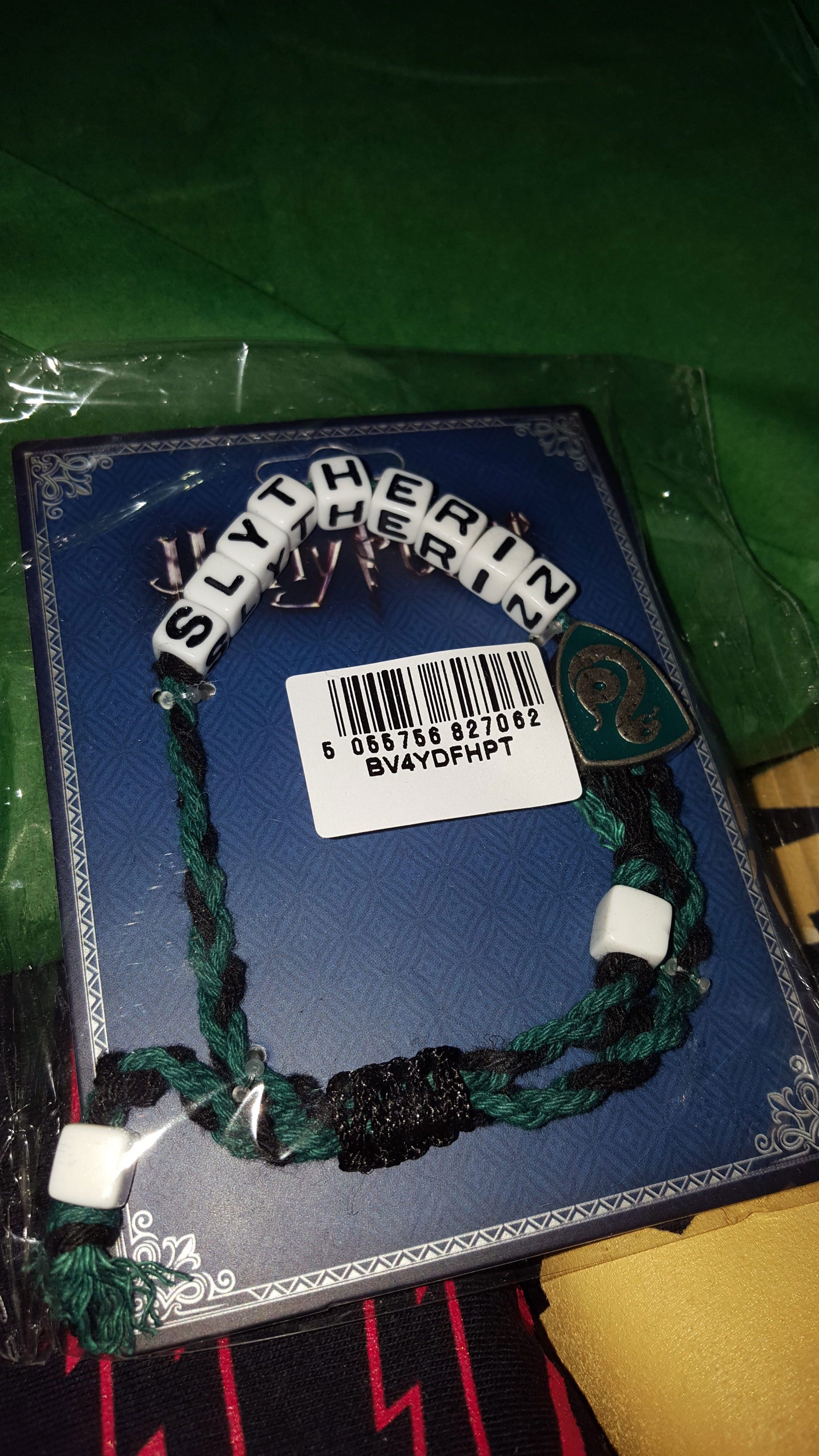 """Slytherin bracelet in green and black thread, with alphabet blocks that spell out """"Slytherin"""""""