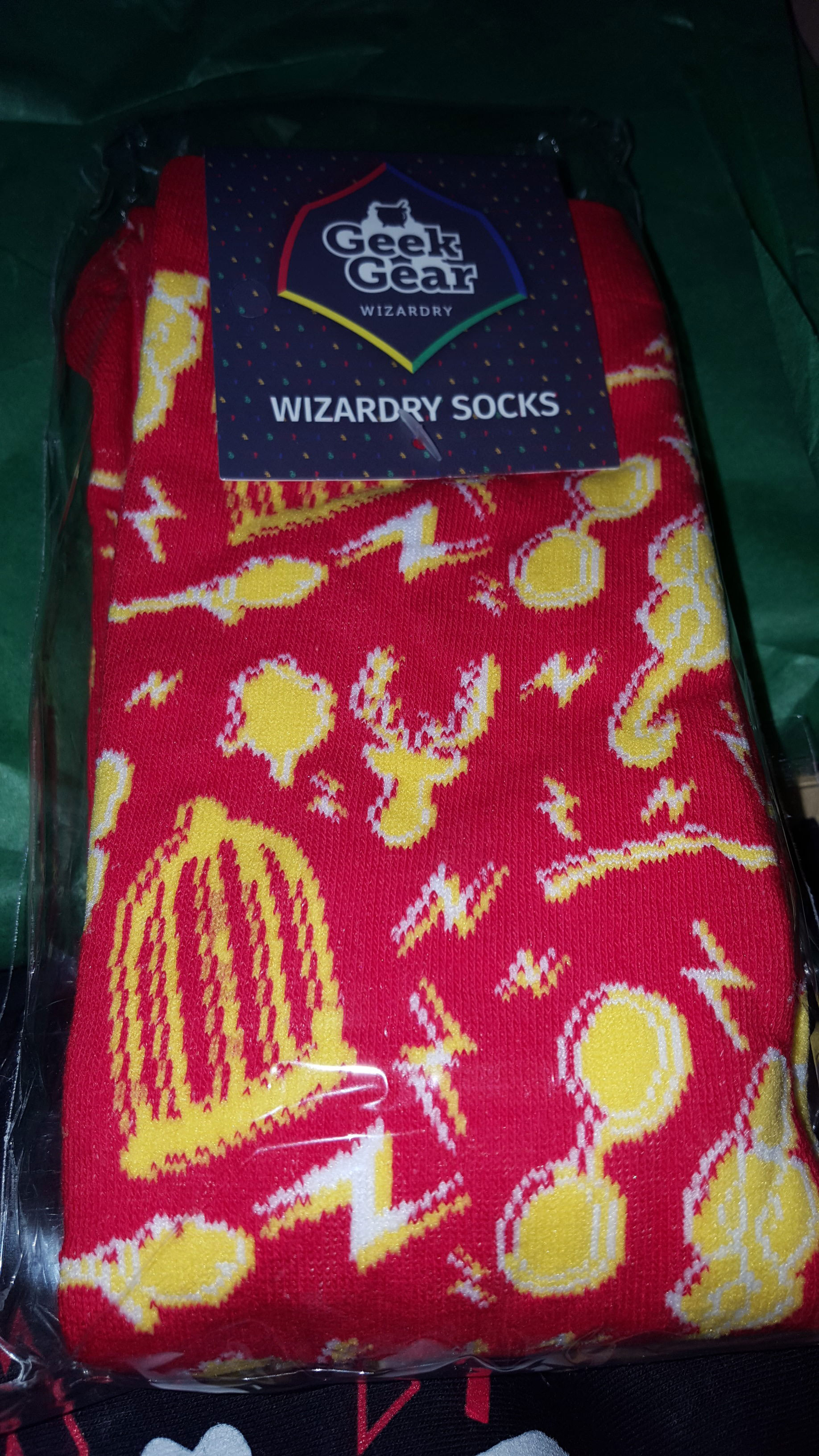 Wizardy socks in red, gold, and white, featuring lightning bolts, glasses, Snitches, brooms, stags, Dark Marks, and owl cages