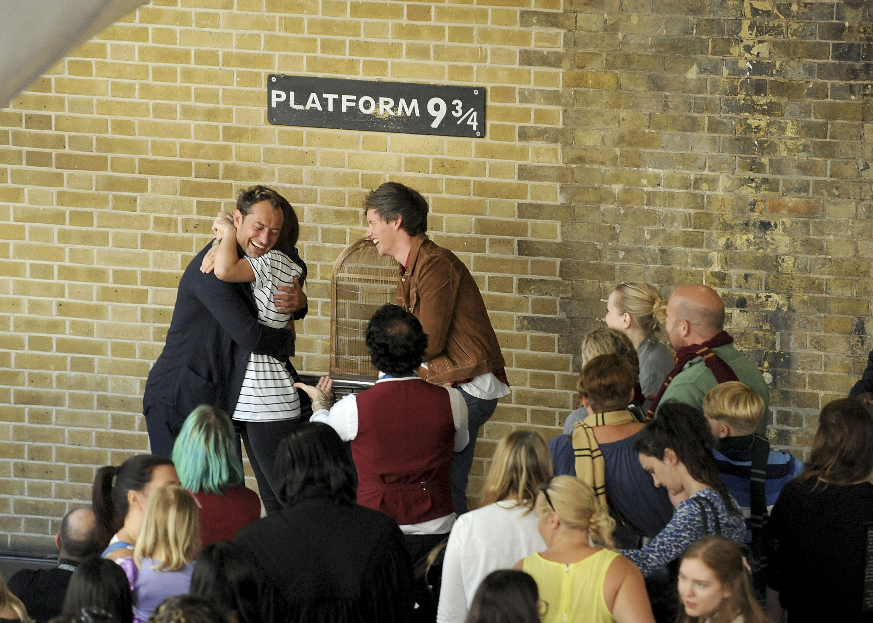 An a official photo of Redmayne and Law surprising fans at Platform 9 3/4 during the Back to Hogwarts Day celebration at King's Cross station on September 1