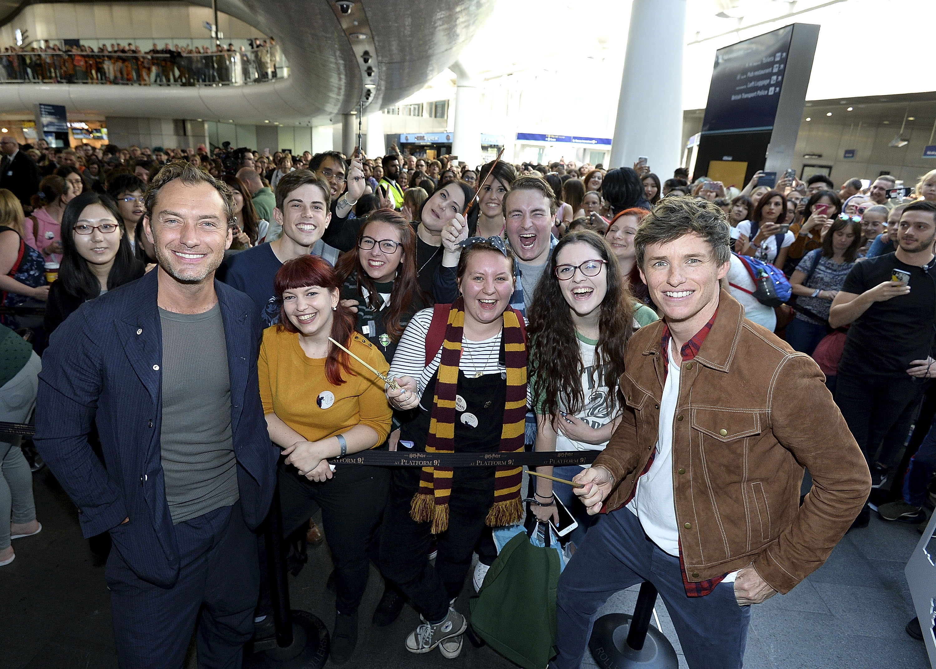 A crowd of fans smiles and cheers as they squeeze into a group photo.