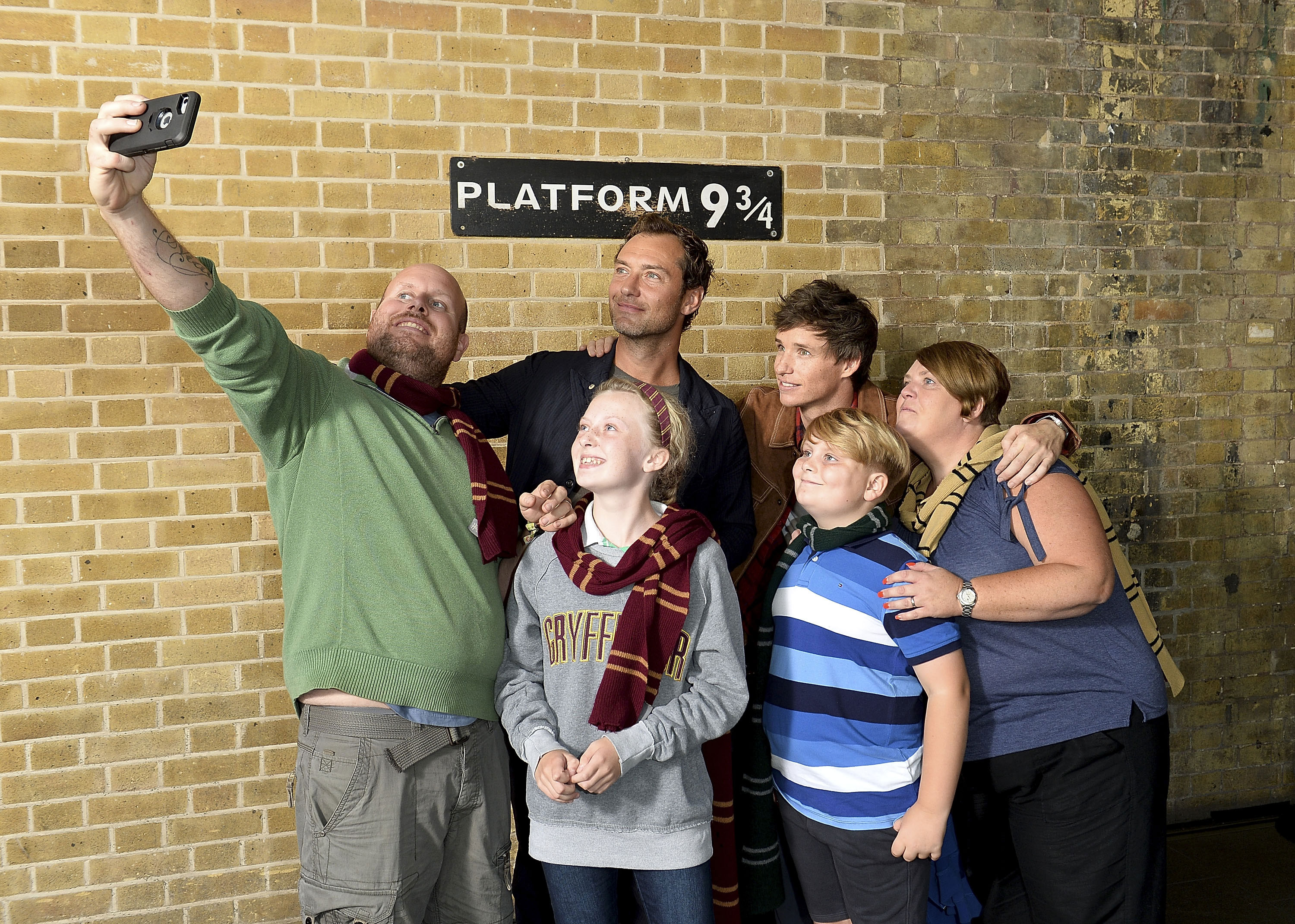 A family of fans – from three different Houses! – snaps a quick selfie with Law and Redmayne.