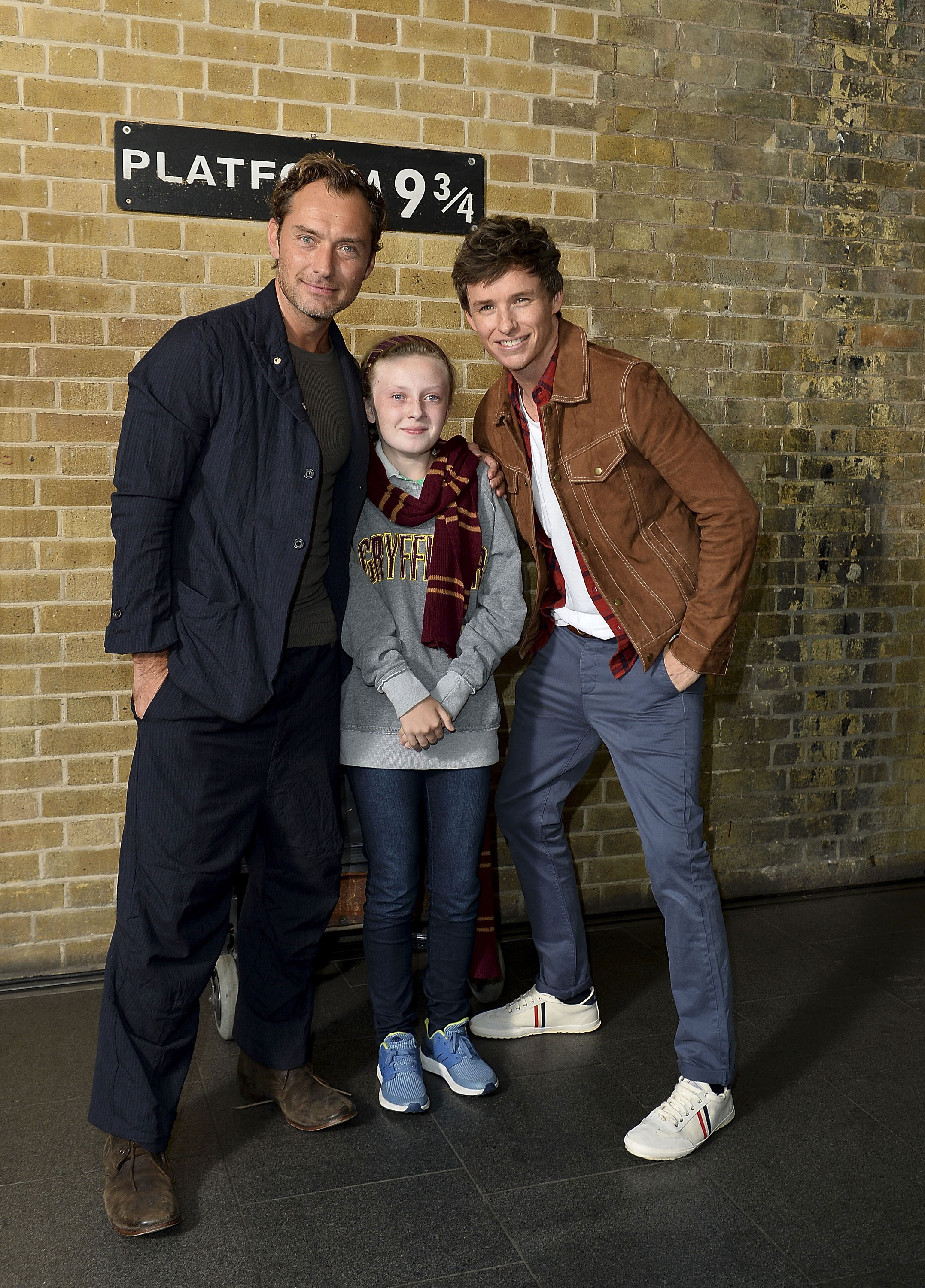 A lucky little Gryffindor gets her photo taken with Law and Redmayne at Platform 9 3/4.