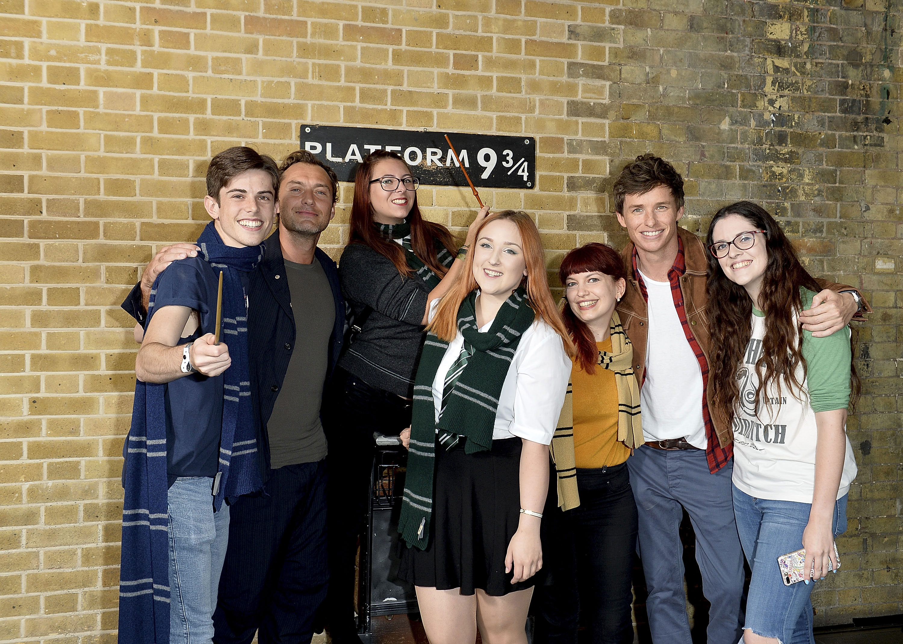 A group of fans from all the Houses poses with Law and Redmayne at Platform 9 3/4.