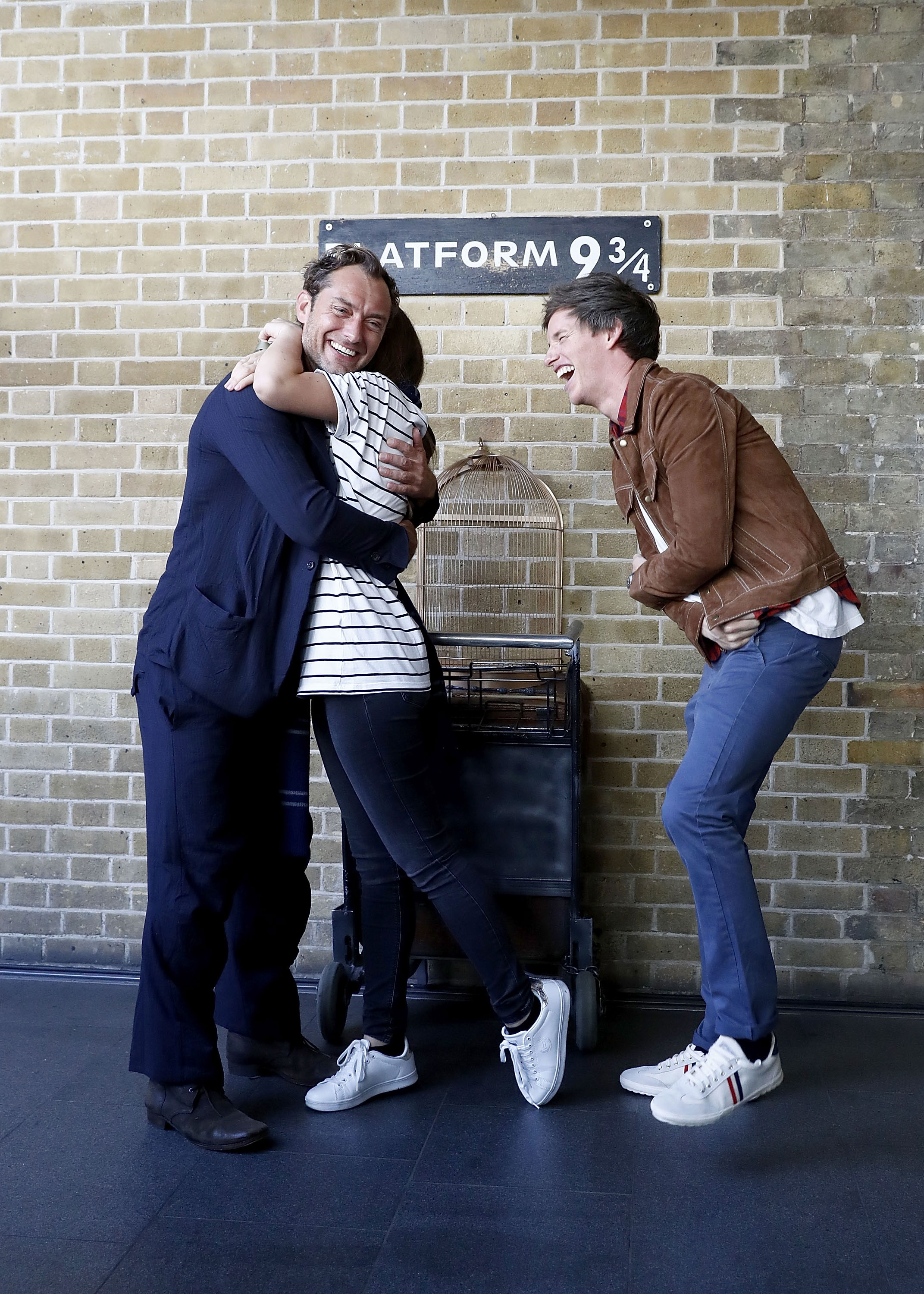 A lucky fan gives Law a hug as Redmayne laughs.