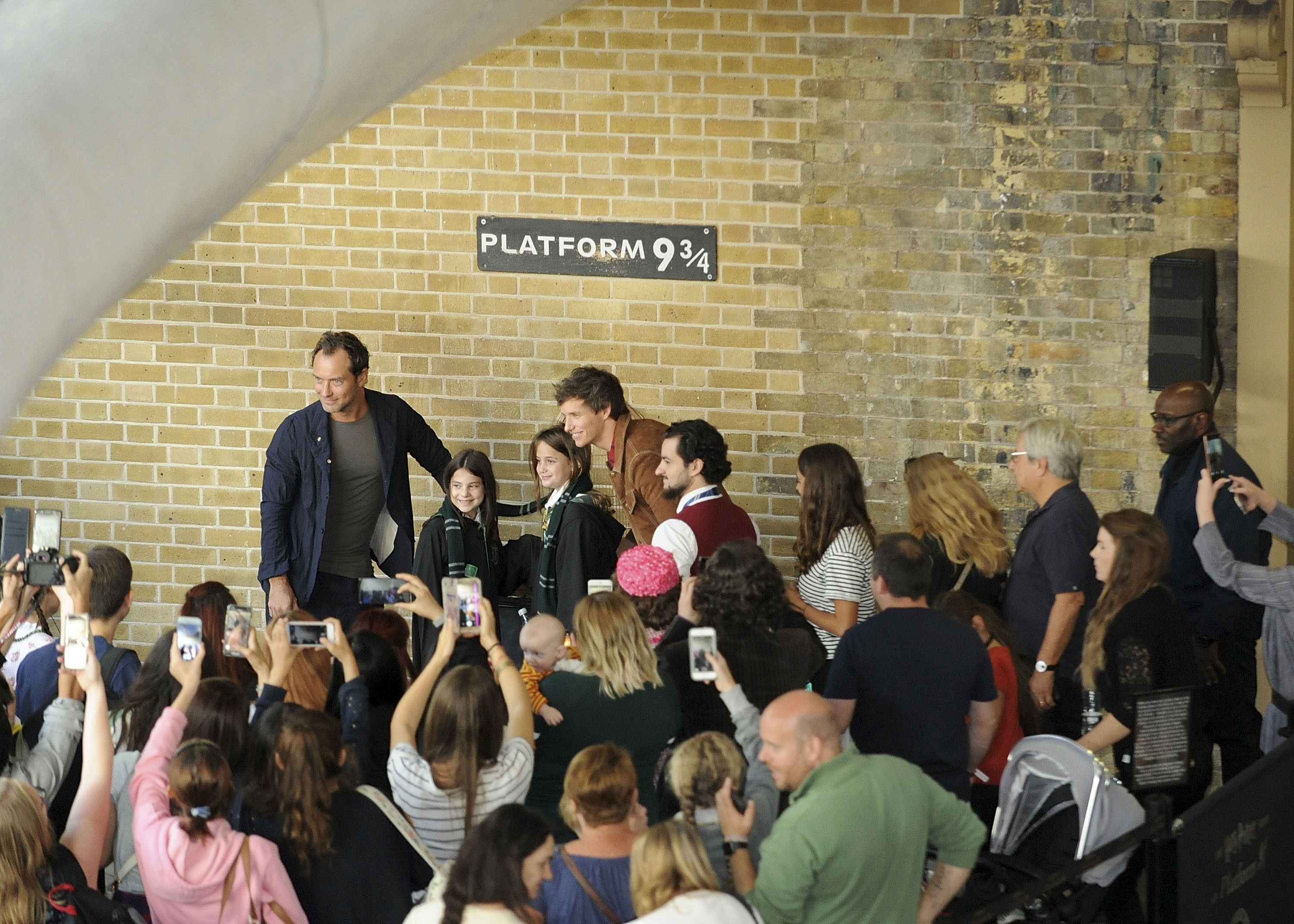 Law and Redmayne pose with two young fans celebrating Back to Hogwarts Day.