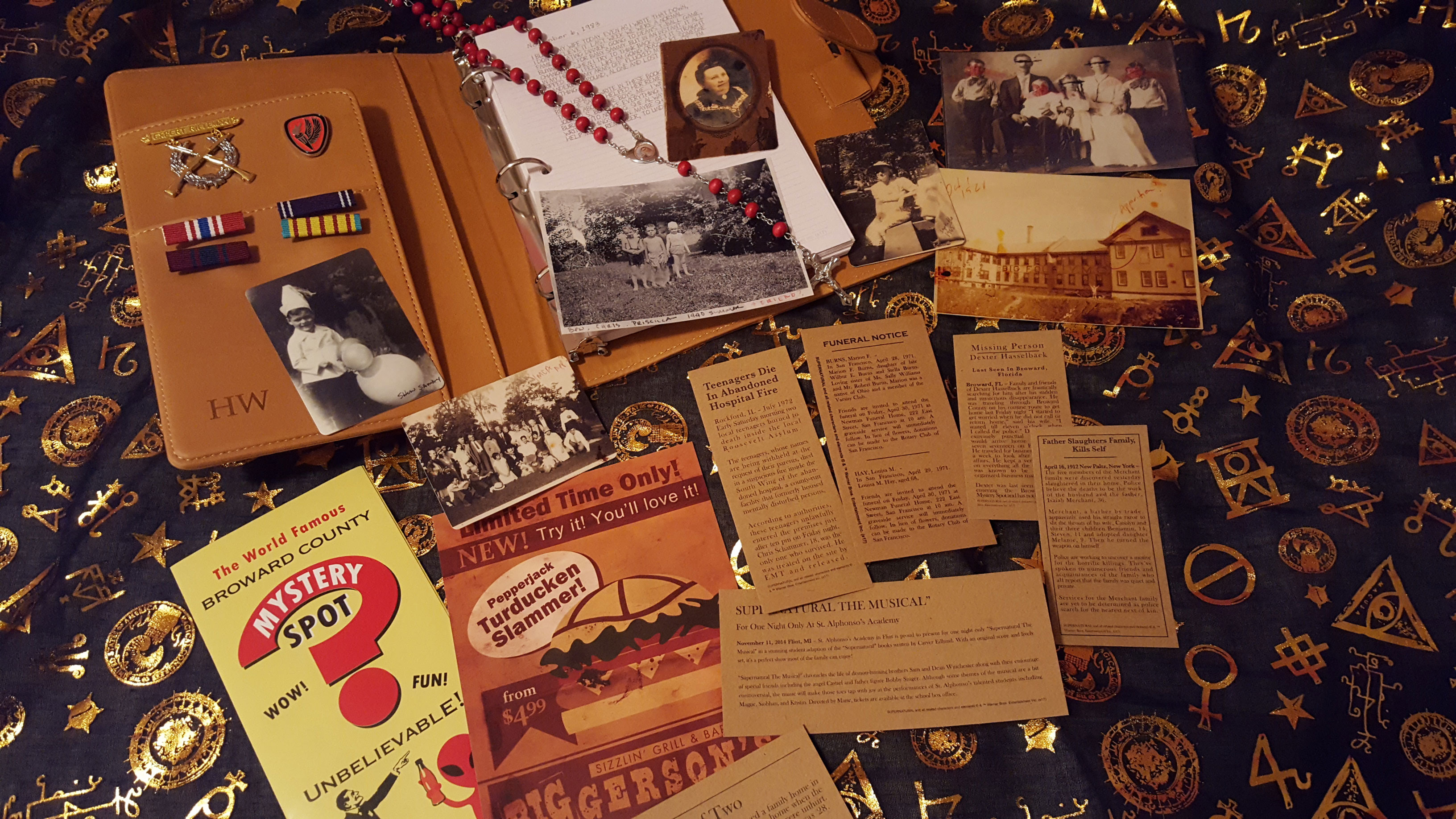 John Winchester's replica hunting journal, medals, photos, newspaper clippings, and rosary