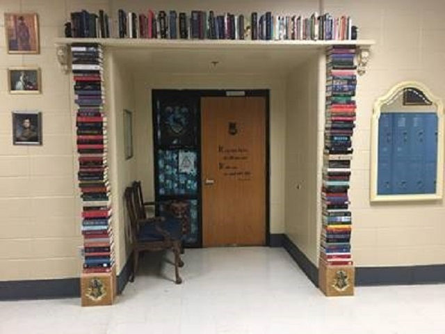 This classroom has an entrance surrounded by books with a glimpse of the portraits lining the hallway.
