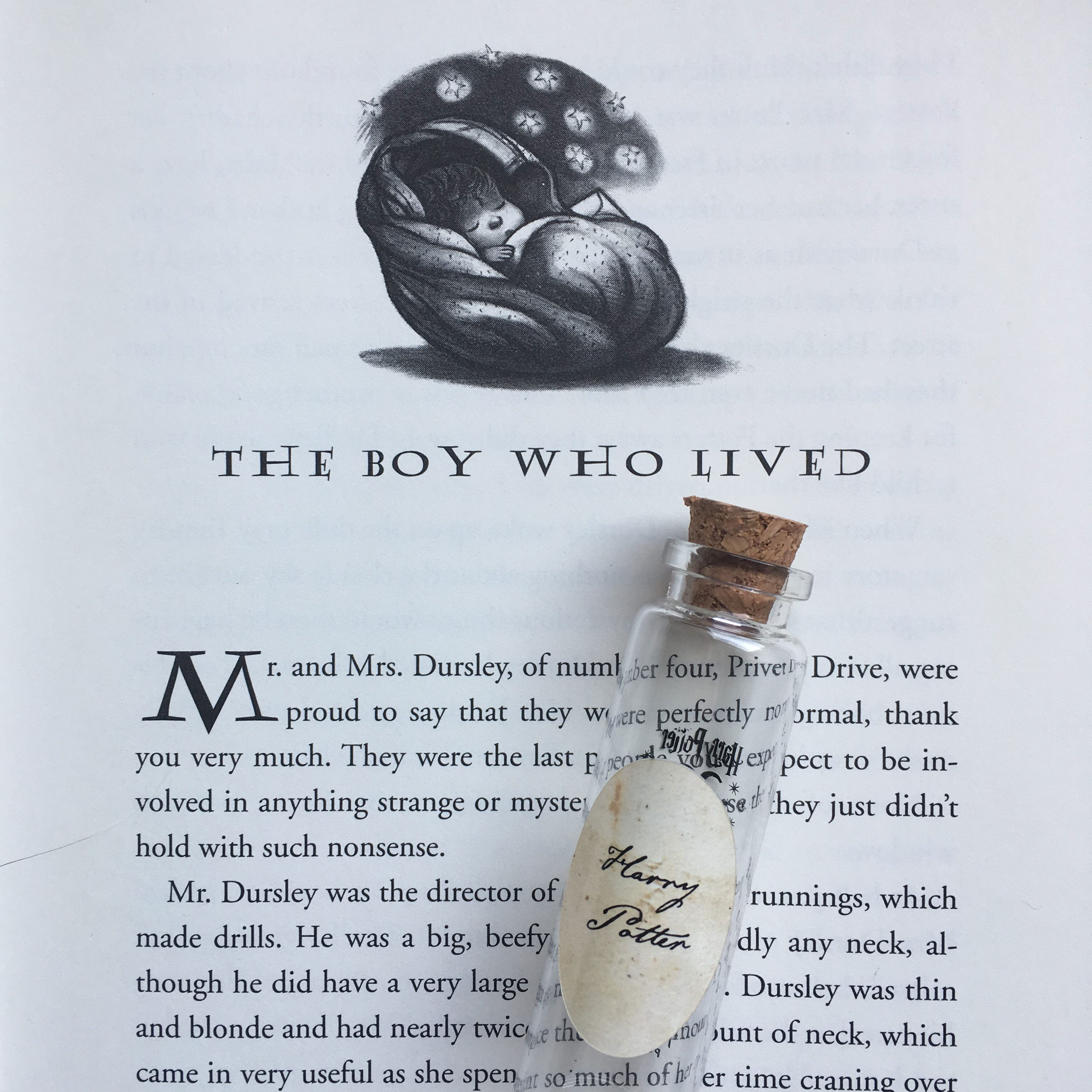 "Harry Potter's Pensieve vial lying on top of the first page of Chapter 1, ""The Boy Who Lived,"" in ""Harry Potter and the Sorcerer's Stone"""