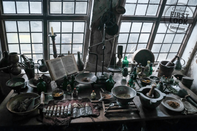 This set photo shows a workstation full of ingredients and magical instruments.