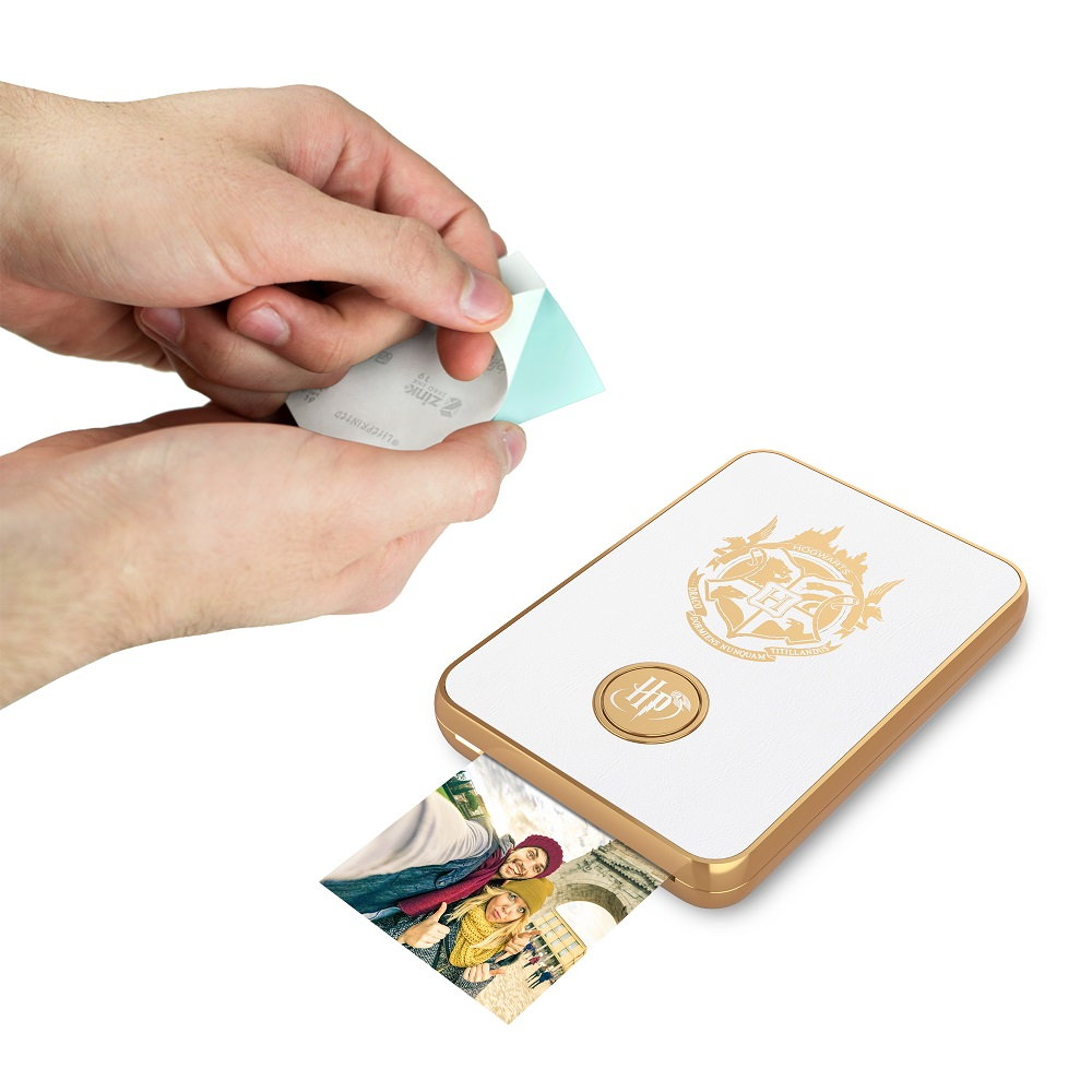 Harry Potter Magic Photo and Video Printer in white, showing the protective backing being removed from the photo sticker paper