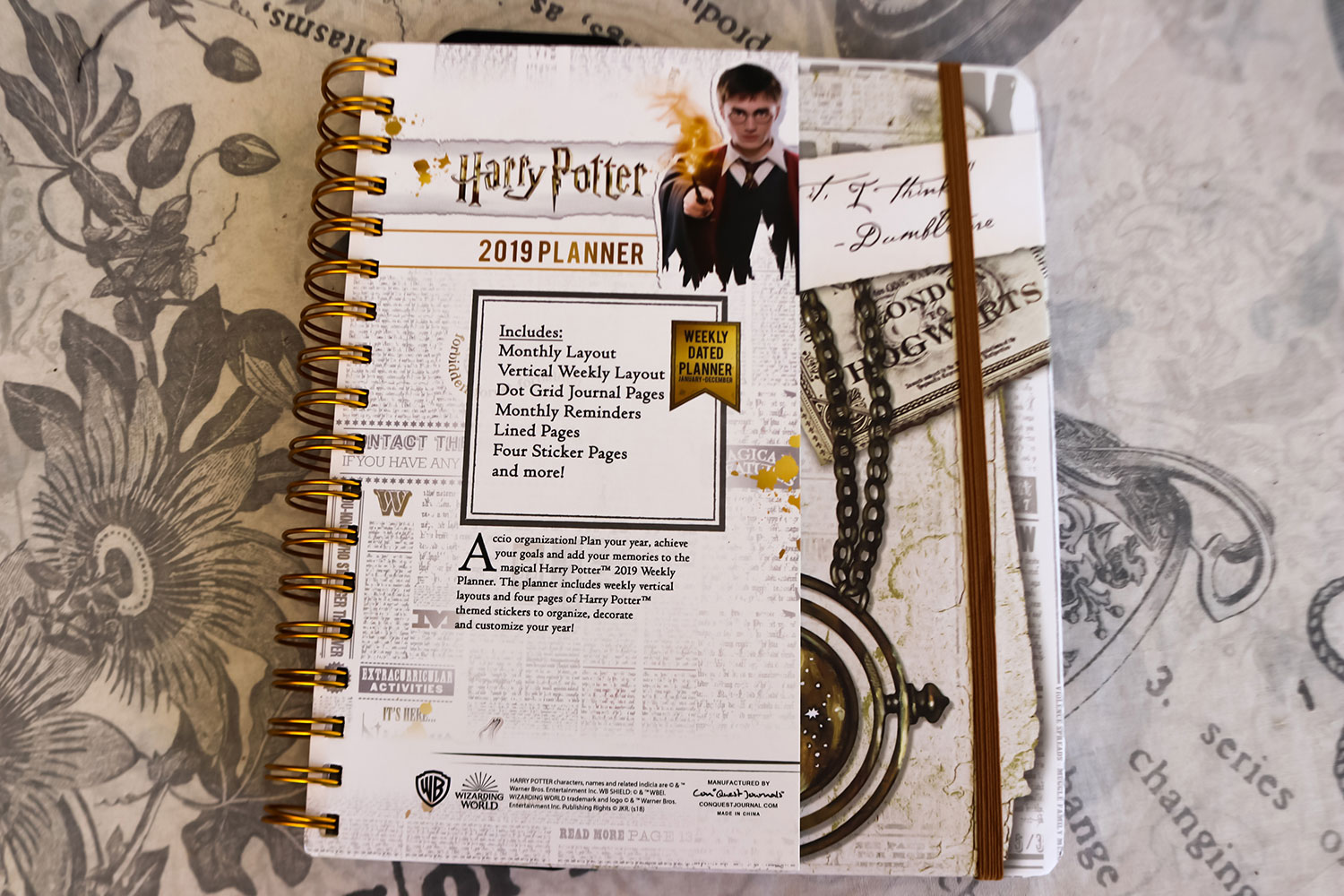 Front cover for Harry Potter 2019 weekly planner featuring Harry Potter with his wand lit, plus the time turner and a Hogwarts Express ticket