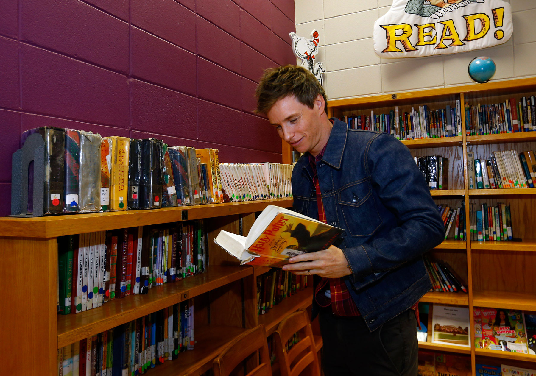 """Eddie Redmayne from """"Fantastic Beasts: The Crimes of Grindelwald"""" reads a book as he helps celebrate Wizarding World Day at Parkside Middle School in Baileyton, AL.  (Photo by Butch Dill/Getty Images)"""