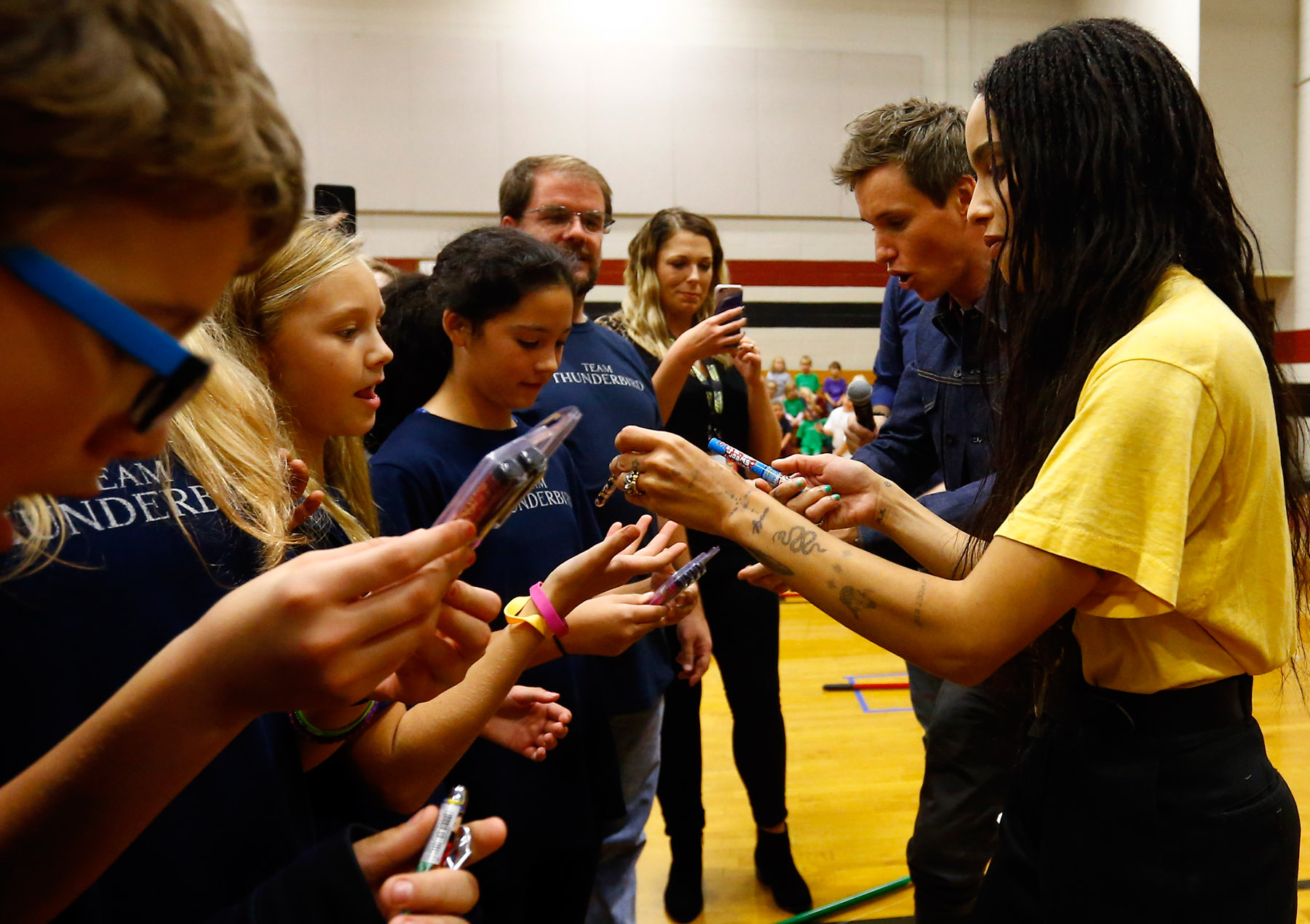 """Eddie Redmayne and Zoë Kravitz from """"Fantastic Beasts: The Crimes of Grindelwald"""" hand out prizes to students to help celebrate Wizarding World Day at Parkside Middle School in Baileyton, AL.  (Photo by Butch Dill/Getty Images)"""