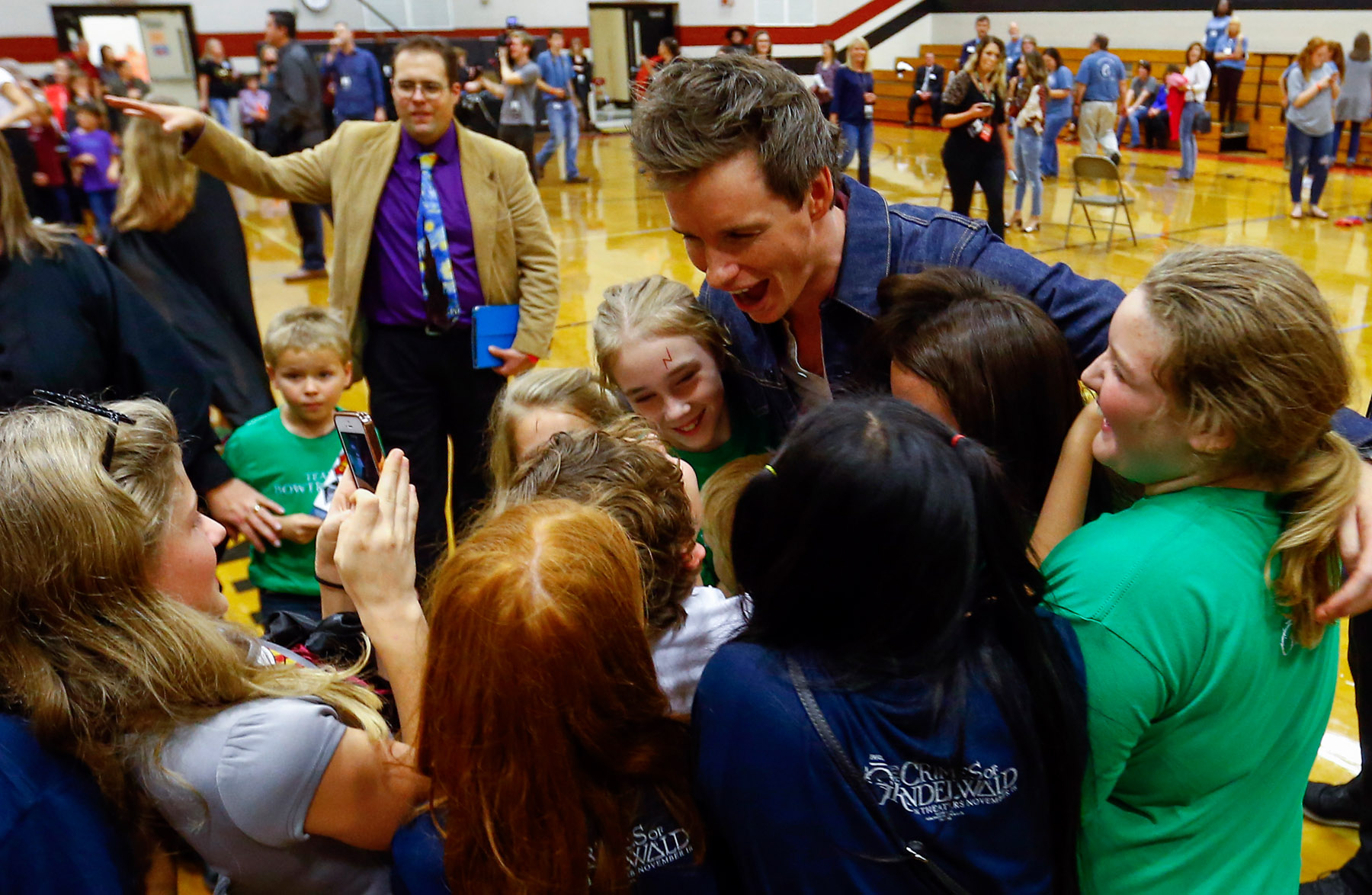 """Eddie Redmayne from """"Fantastic Beasts: The Crimes of Grindelwald"""" says goodbye to students after helping them celebrate Wizarding World Day at Parkside Middle School in Baileyton, AL.  (Photo by Butch Dill/Getty Images)"""