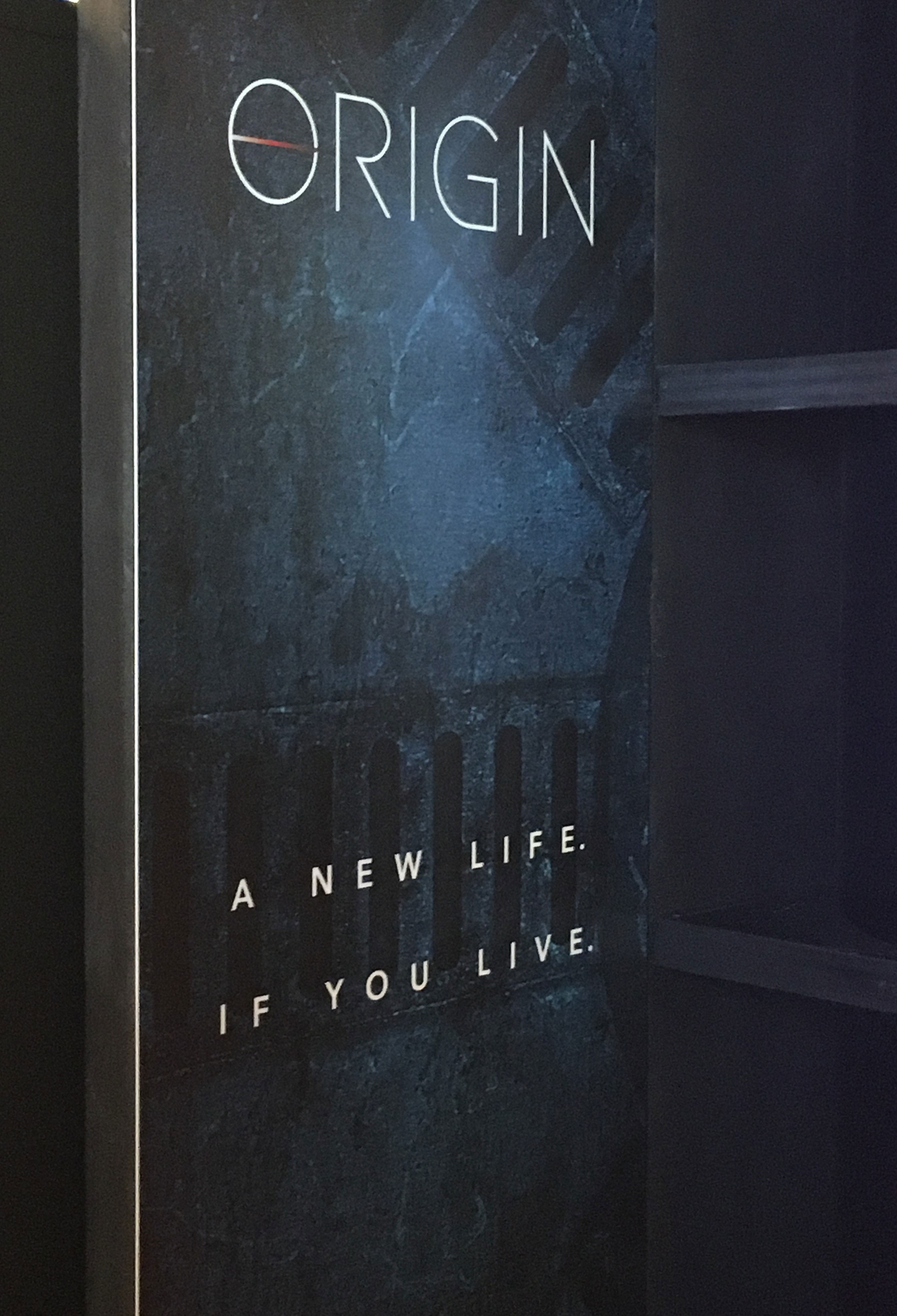 """Poster with """"A New Life If You Live"""" tagline at the """"Origin"""" series premiere"""