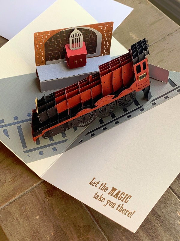 Pop-Up Hogwarts Express Card from Insight Editions showing the red steam engine car with a school trunk and Hedwig's cage waiting on the platform