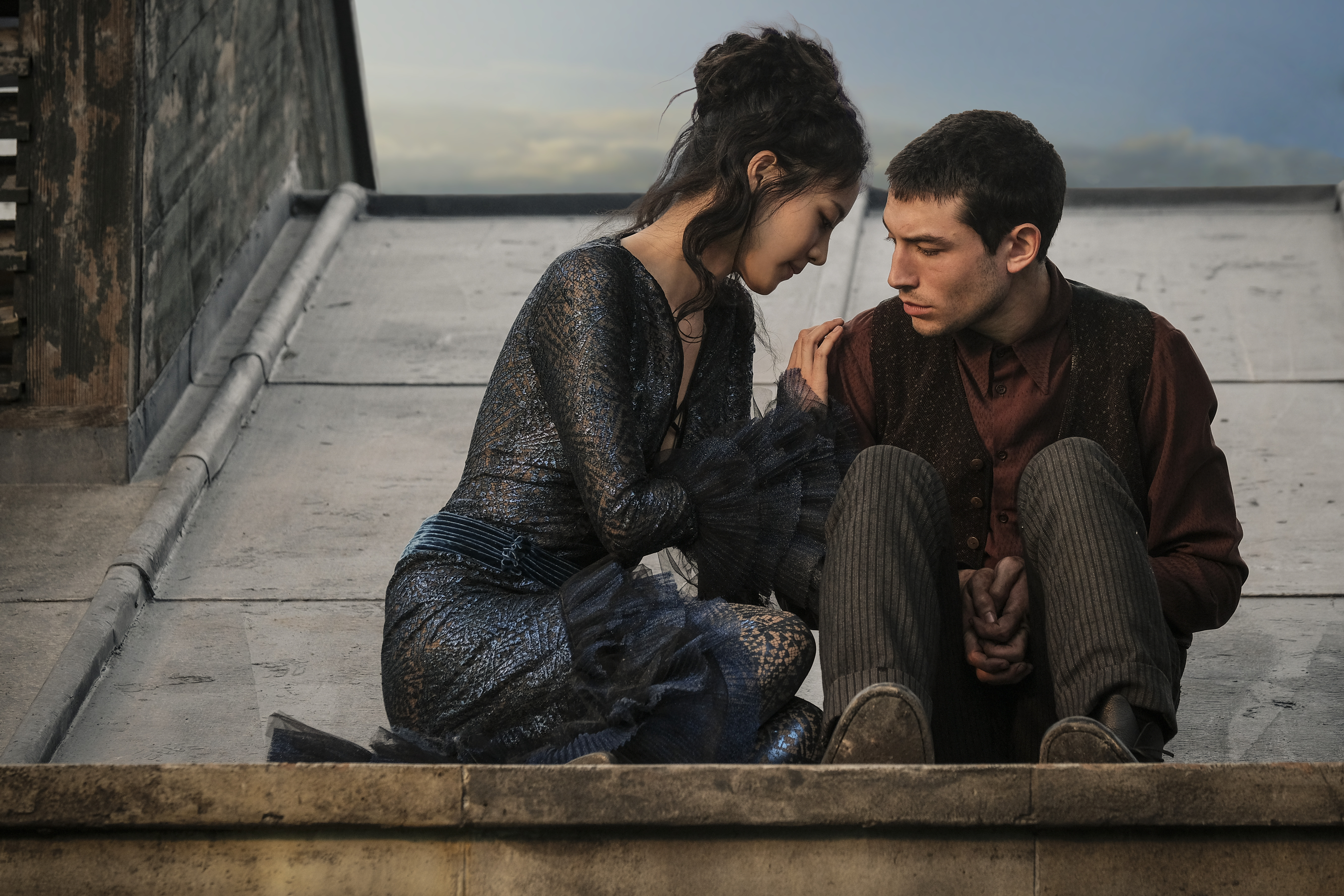 The Maledictus and Credence sit together on a rooftop.