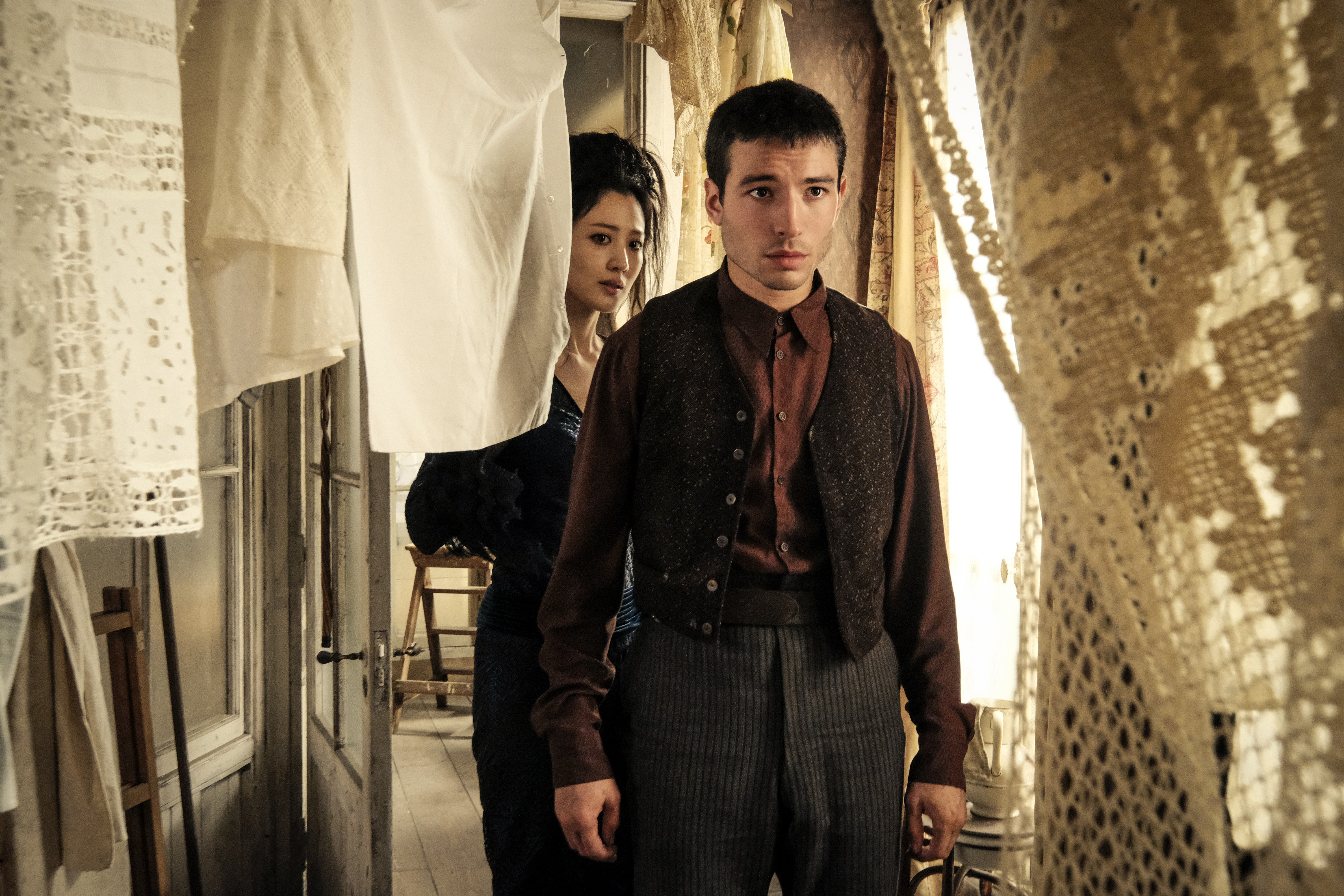 Credence and the Maledictus peer through hanging fabric.