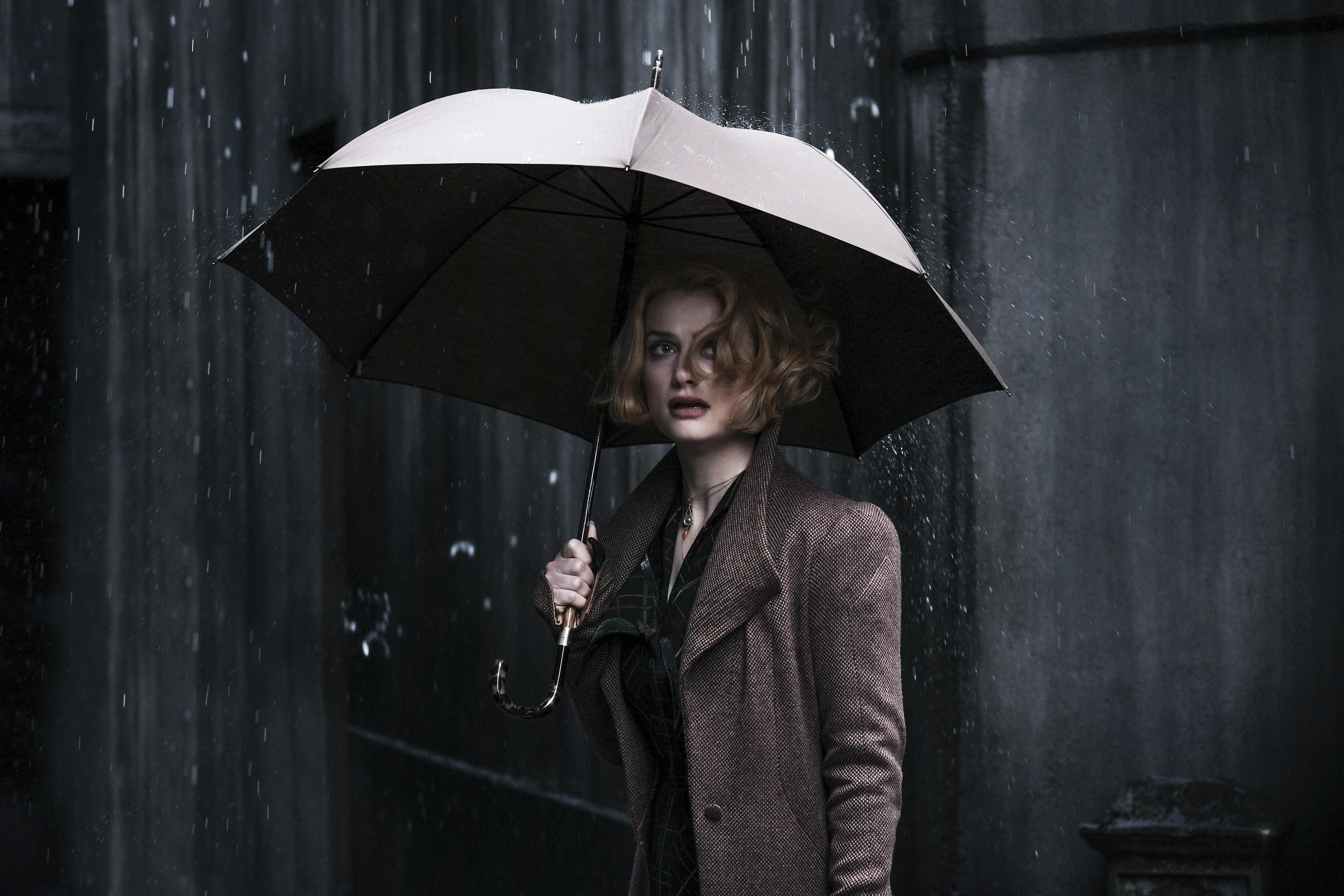 Queenie Goldstein stands in the rain.