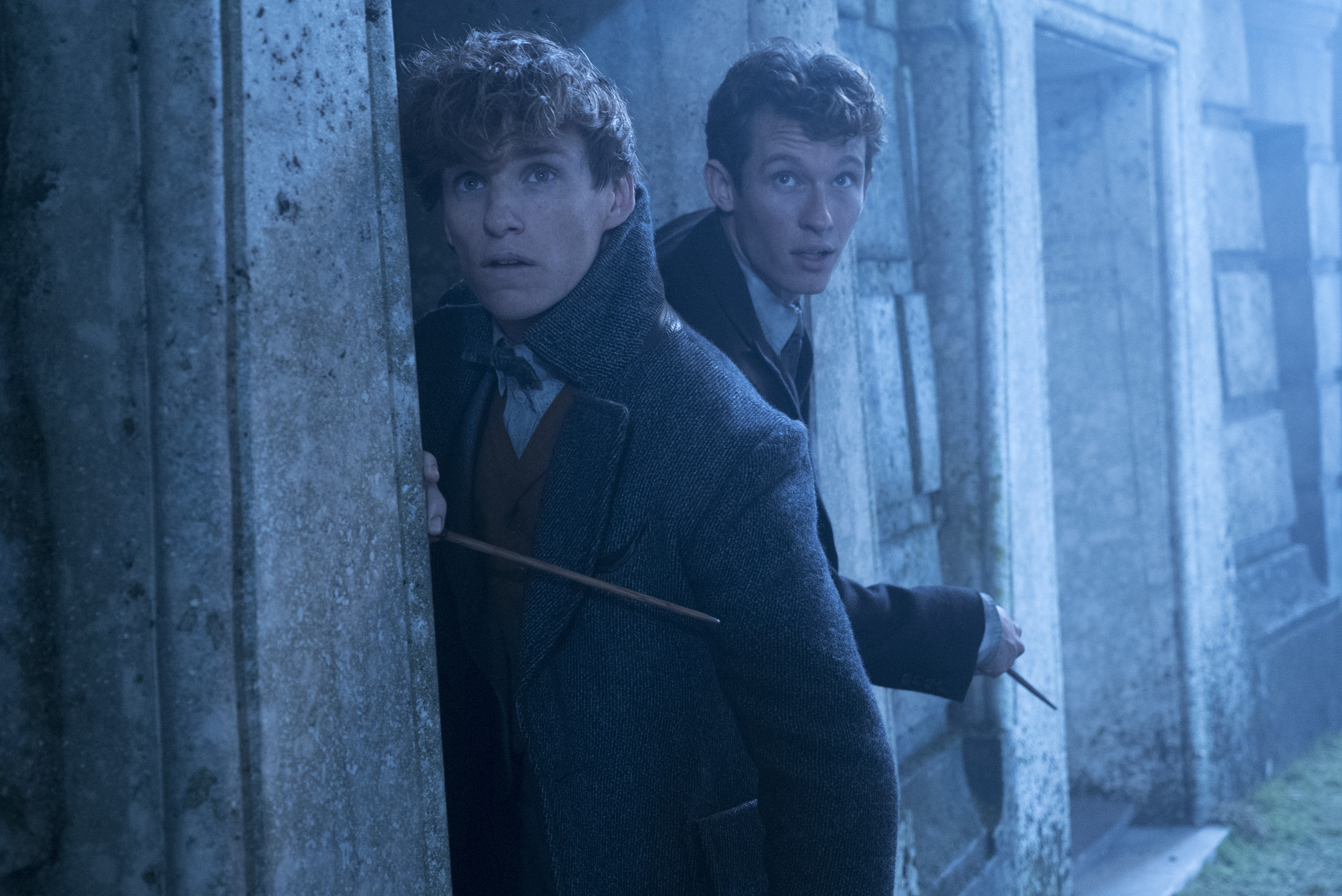 Newt and Theseus Scamander scout around a corner.