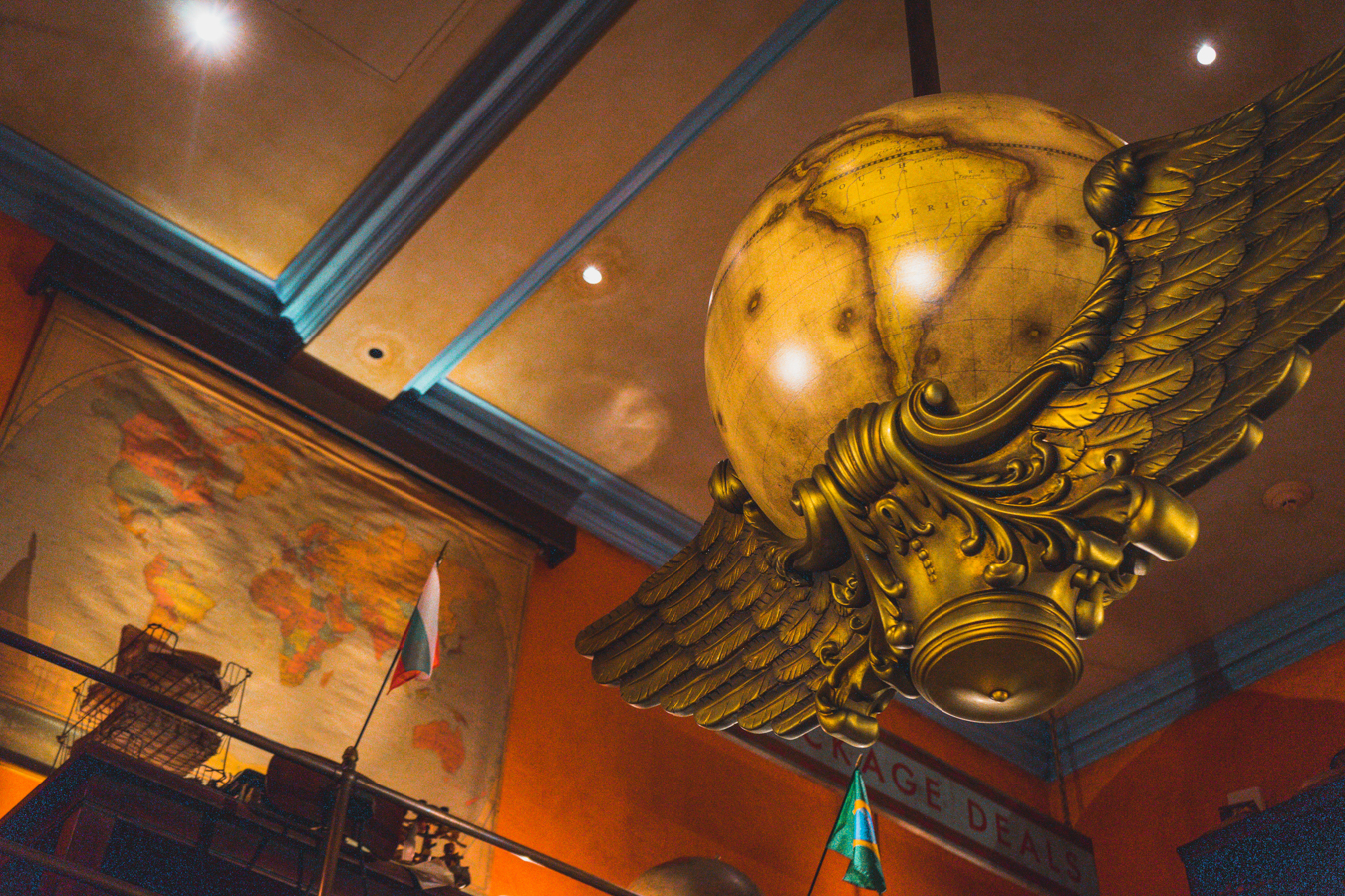 A large globe is supported by golden wings in the shop.