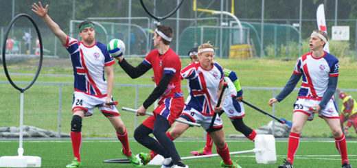 Chaser in red jersey holding a quaffle and trying to score in hoops. One female chaser in UK jersey is trying to stop him. Keeper in UK jersey is standing in front of hoops. One chaser in UK jersey is watching them.