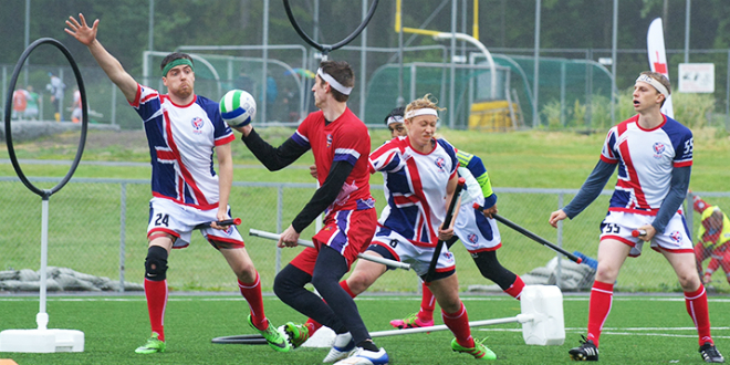 A chaser in a red jersey attempts to score against the United Kingdom while UK team members look on.