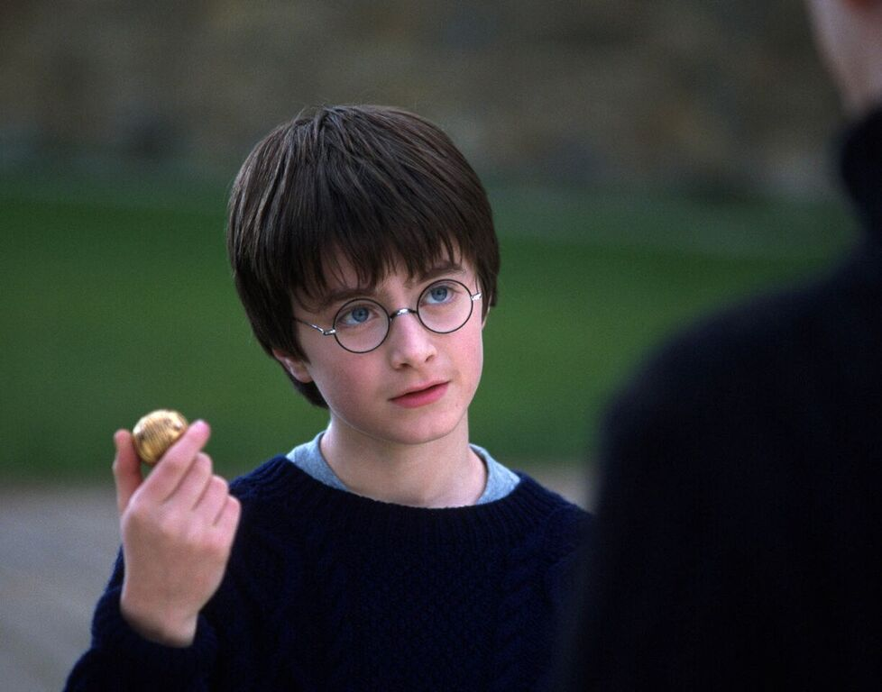 Harry holds the Golden Snitch during his first Quidditch lesson.