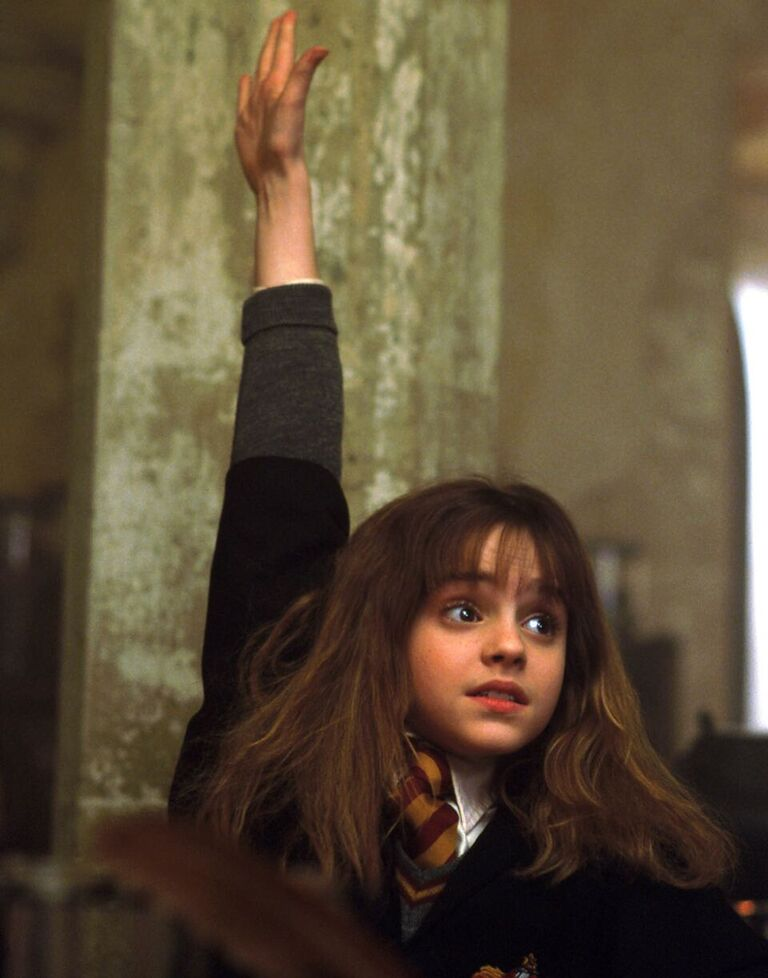 Hermione raises her hand to answer a Potions question.