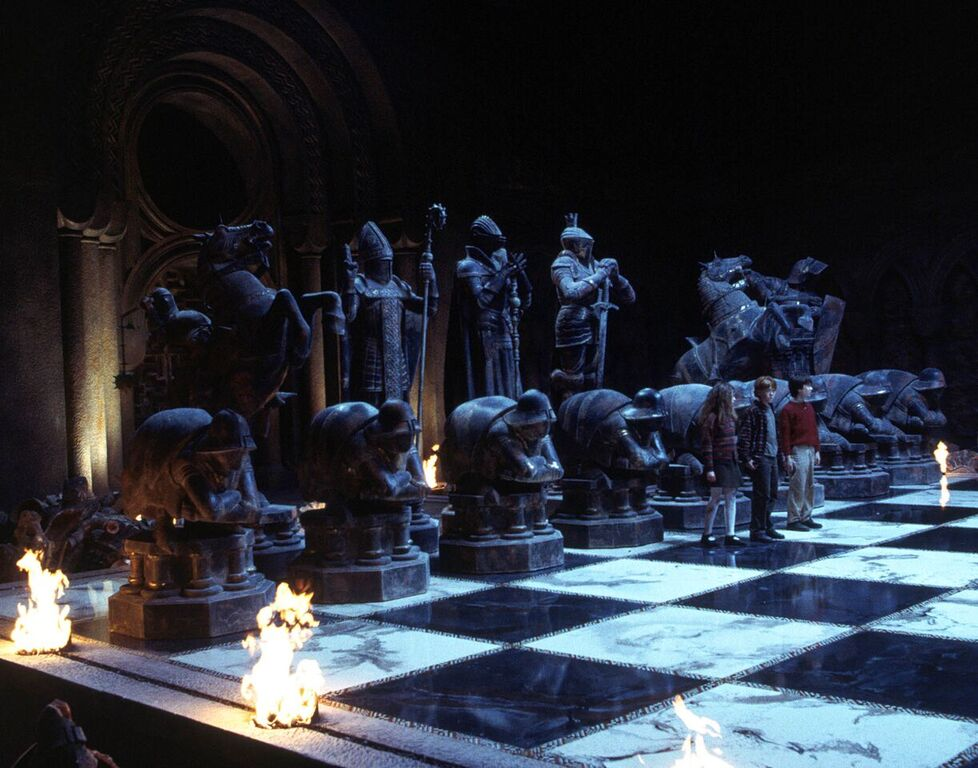 Harry, Ron, and Hermione begin playing a game of giant wizard chess on their path to the Sorcerer's Stone.