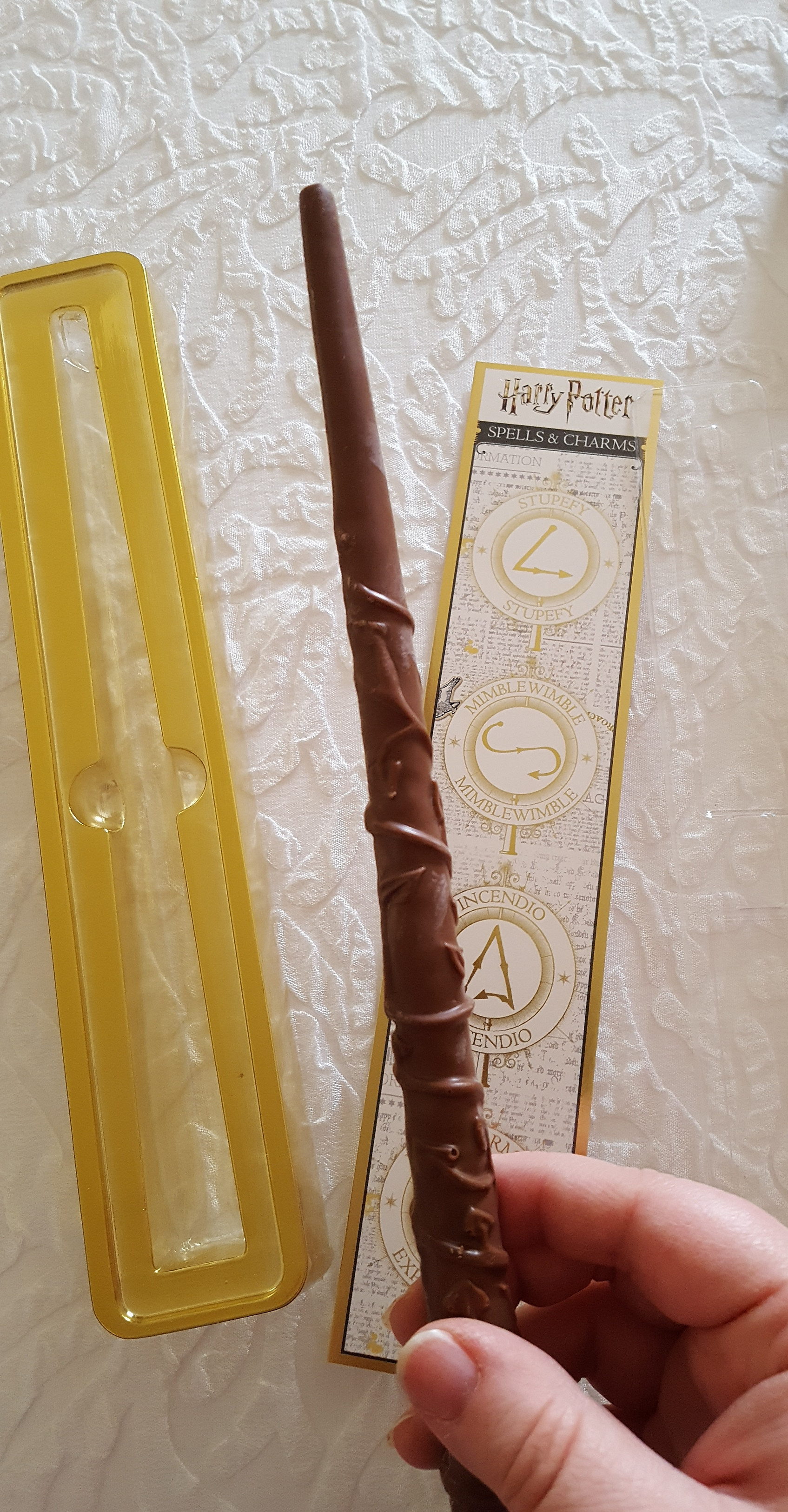 Jelly Belly Hermione Granger chocolate wand, out of the box, with the wizard spell sheet in the background