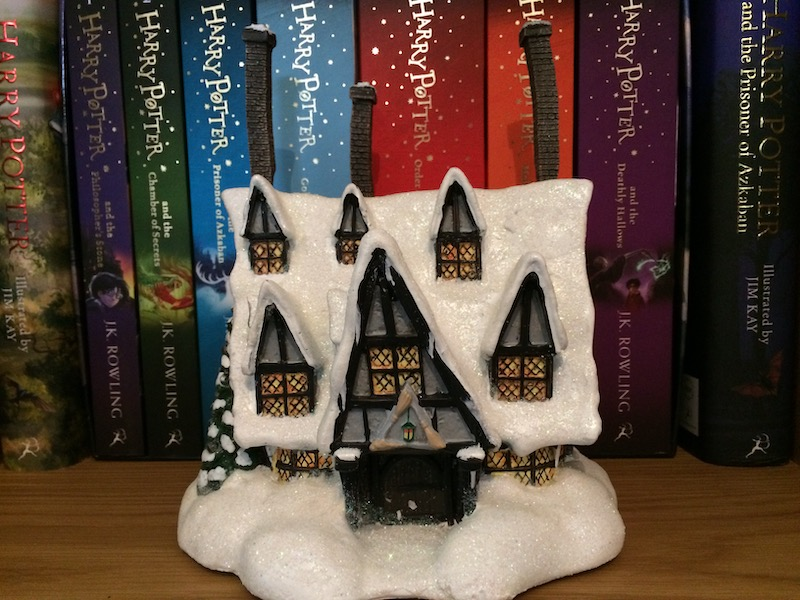 "Covered in glittery snow, the ""THREE BROOMSTICKS PUB™"" looks quaint and quirky with its crooked chimneys and windows."