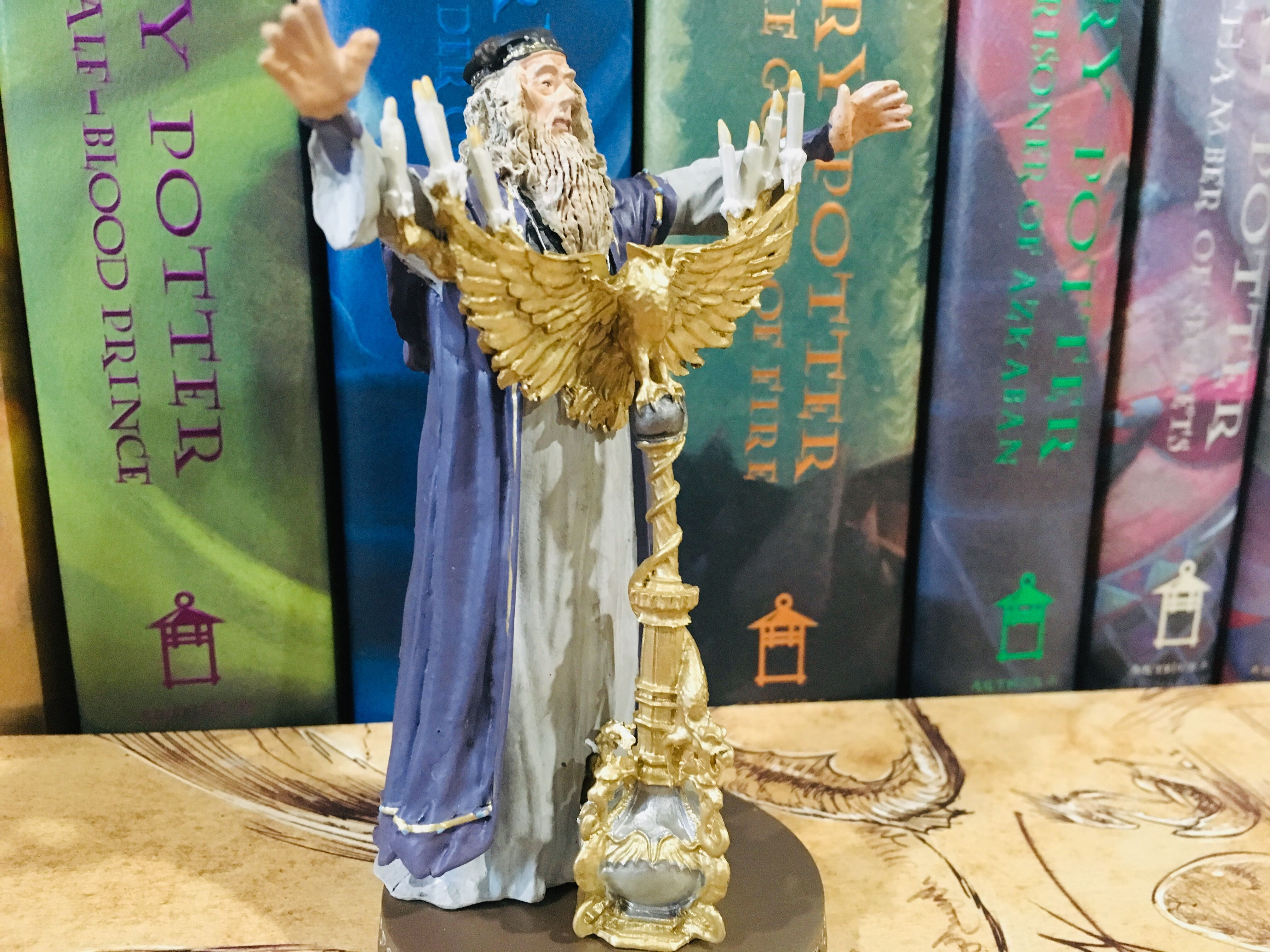 Dumbledore stands with his arms extended, dressed in beautiful flowing robes and standing atop his golden lectern.
