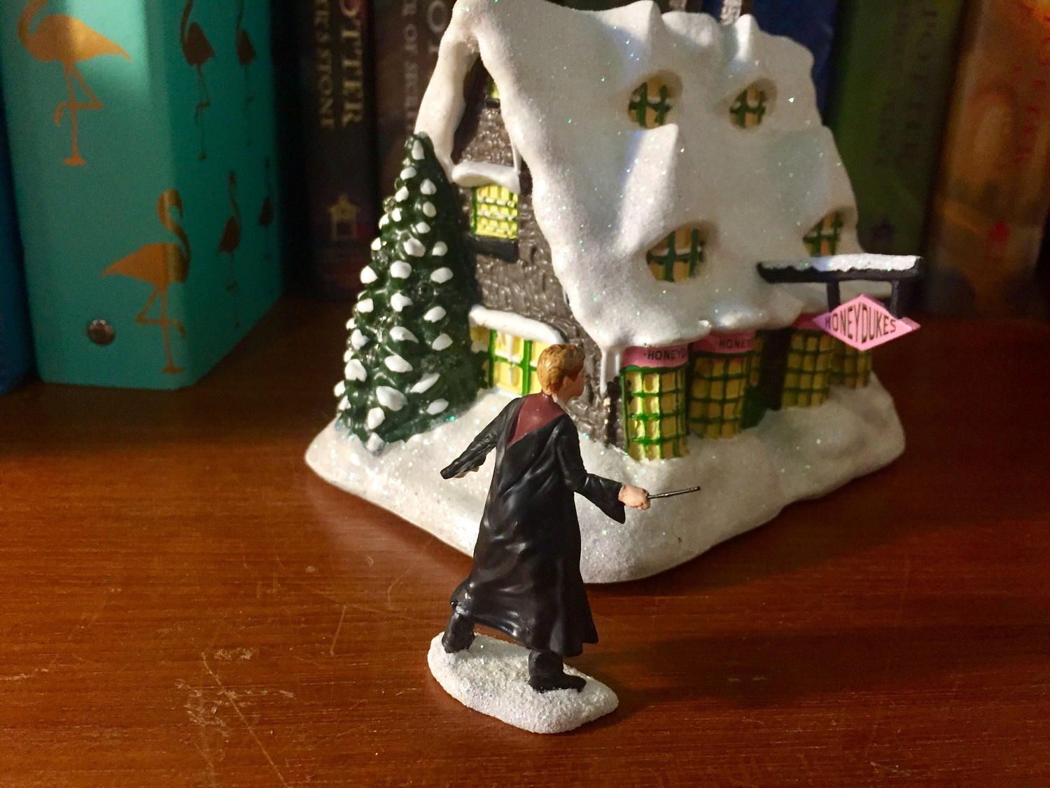 "The Bradford Exchange ""HONEYDUKES™"" (side view) with ""RON WEASLEY™"" (back view), showing the glittering snow details of the roof and base of the figurine."
