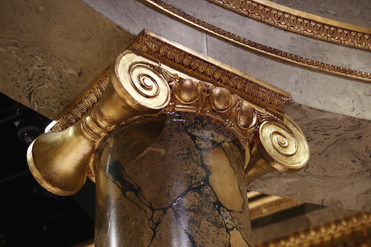 The incredible set design features a convincing marble effect and gold masonry.